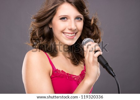 Young and smiling teenager with microphone in front of grey background