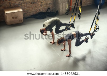 Young and sporty. Top view of a couple in sportswear training with Trx fitness straps at gym