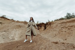 Young and stylish brunette girl posing dynamically in a beige trench coat in the sand pit.