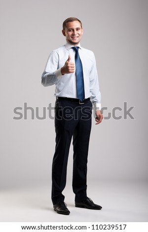 Young and successful businessman showing thumbs up