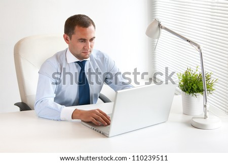 Young and successful businessman typing on his laptop