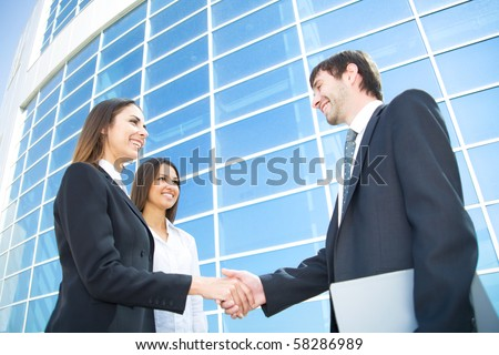Young and successful businesspeople shake hands against the modern office building