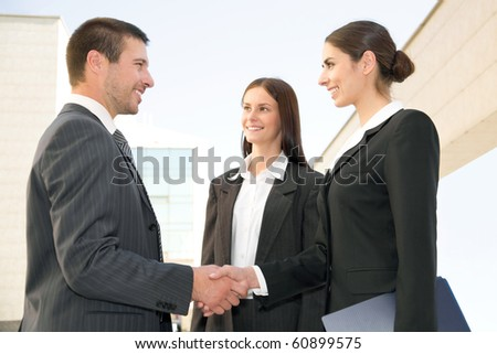 Young and successful businesspeople shake hands against the modern office building - stock photo