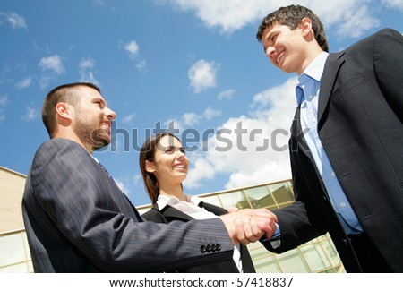Young and successful businesspeople shake hands against the sky