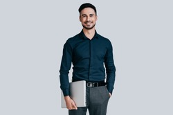 Young and successful. Good looking young man in shirt carrying laptop and looking at camera with smile while standing against grey background