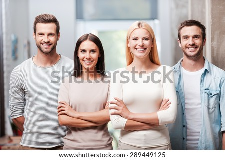 Young and successful team. Four young business people in smart casual wear standing close to each other and smiling discussing  Stockfoto ©
