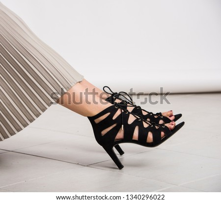 Young and trendy female legs with black high heeled shoes with heels on the ground. Studio abstract shot, body parts. #1340296022