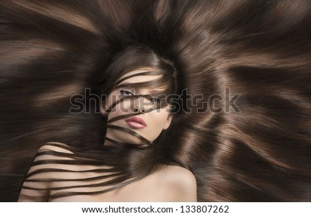 young and very nice woman  with long  hair laying down and some locks on the face and the neck