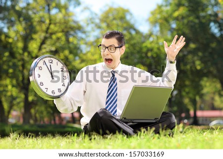 Young angry businessperson with laptop sitting on green grass and looking at clock in a park