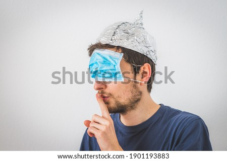 Young angry man with face mask over the eyes and aluminum hat is doing a psst! gesture Stock photo ©