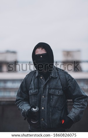 Young anonymous graffitist hide his face with mask, hood and glasses. Preparing of a spray paint stock photo