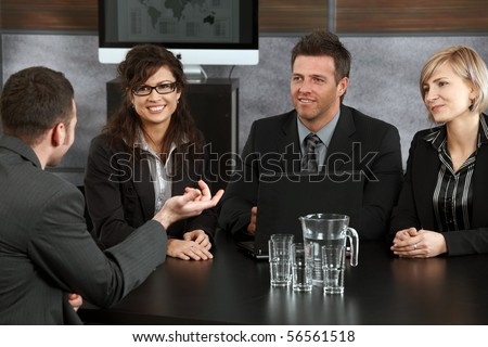 Young applicant explaining to panel of happy businesspeople during job interview in office.