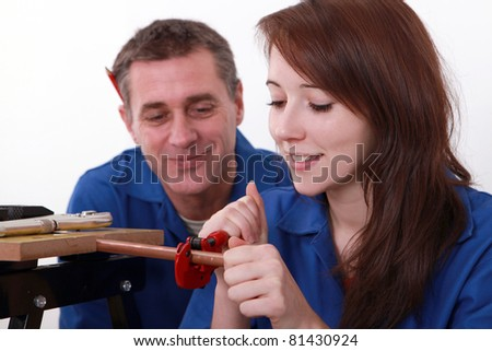 Young apprentice plumber with mentor