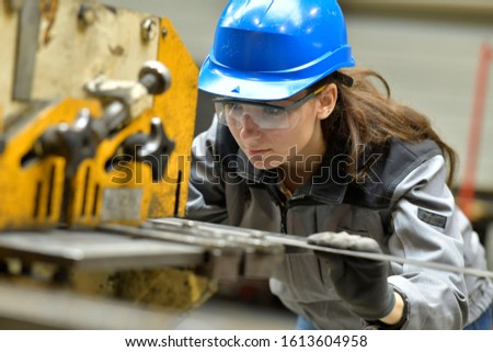 Young apprentice using steelworks machine Foto stock ©