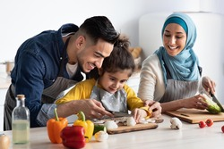 Young Arab Father Showing How To Chop Mushrooms To His Little Daughter While They Cooking Healthy Tasty Food Together At Home, Happy Muslim Family Of Three Enjoying Preparing Vegetarian Meal