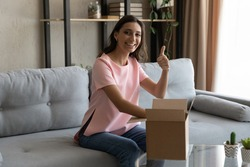Young arab female loyal client of delivery service web shop open package show thumb up positive feedback. Portrait of indian lady blogger unpack box with ordered product look at camera recommend goods