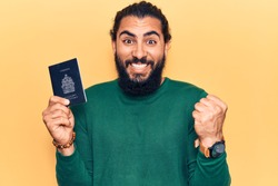 Young arab man holding canada passport screaming proud, celebrating victory and success very excited with raised arm