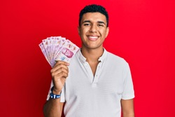Young arab man holding mexican pesos looking positive and happy standing and smiling with a confident smile showing teeth