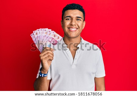 Young arab man holding mexican pesos looking positive and happy standing and smiling with a confident smile showing teeth  Foto stock ©