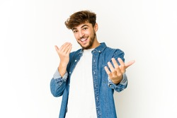 Young arab man on white background pointing with finger at you as if inviting come closer.