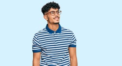 Young arab man wearing casual clothes and glasses looking away to side with smile on face, natural expression. laughing confident.