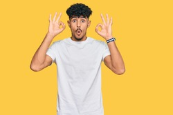 Young arab man wearing casual white t shirt looking surprised and shocked doing ok approval symbol with fingers. crazy expression