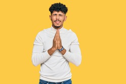 Young arab man wearing casual winter sweater begging and praying with hands together with hope expression on face very emotional and worried. begging.