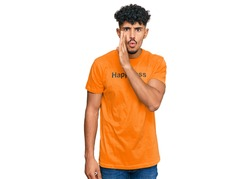 Young arab man wearing tshirt with happiness word message hand on mouth telling secret rumor, whispering malicious talk conversation