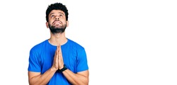 Young arab man with beard wearing casual blue t shirt begging and praying with hands together with hope expression on face very emotional and worried. begging.