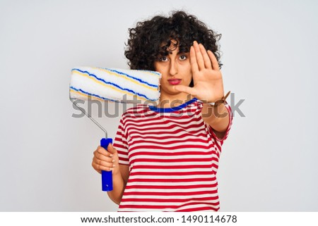 Young arab painter woman with curly hair holding paint roller over isolated white background with open hand doing stop sign with serious and confident expression, defense gesture