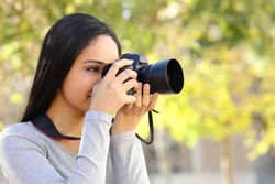 Young Arab woman learning photography in a park with a green unfocused background