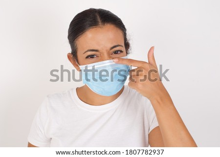 Young arab woman wearing medical mask standing over isolated white background pointing unhappy to pimple on forehead, ugly infection of blackhead. Acne and skin problem