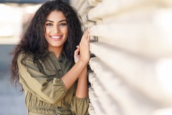 Young Arab Woman with curly hair smiling outdoors