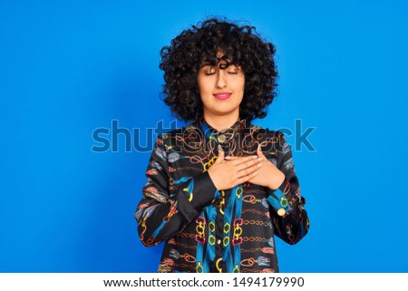 Young arab woman with curly hair wearing colorful shirt over isolated blue background smiling with hands on chest with closed eyes and grateful gesture on face. Health concept.
