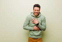 young arabian man laughing out loud at some hilarious joke, feeling happy and cheerful, having fun against flat wall