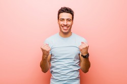 young arabian man shouting triumphantly, laughing and feeling happy and excited while celebrating success against pink wall