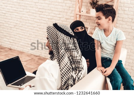 Young Arabic Family Using Laptop on Sofa at Home. Family Sitting on Sofa. Man Using Digital Device. Smiling Boay at Home. Muslim Family. Smiling Boy. Young Arabian Woman. Woman in Black Veil.