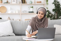 Young arabic woman in hijab watching webinar on laptop and taking notes while sitting on couch at home, free space