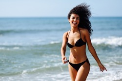 Young arabic woman with beautiful body in swimwear smiling in a tropical beach. Brunette female with curly long hairstyle wearing black bikini.