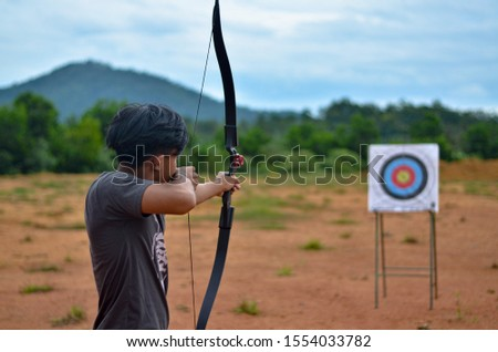 Young archer aiming on the target #1554033782