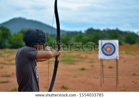 Young archer aiming on the target #1554033785