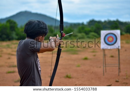 Young archer aiming on the target #1554033788