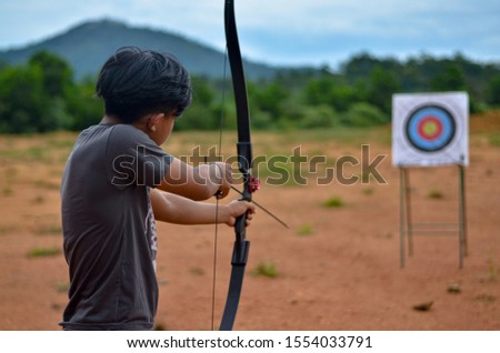 Young archer aiming on the target #1554033791