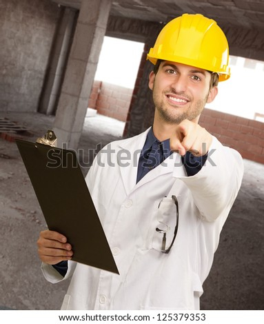 Young Architect Holding Clipboard And Pointing, Indoors