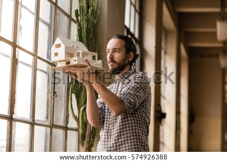 Young architect is looking on the new model in the old industrial space with big factory windows. Man is standing in front of window and holding small model of the house. Color toned image. #574926388