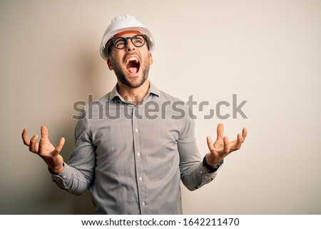Young architect man wearing builder safety helmet over isolated background crazy and mad shouting and yelling with aggressive expression and arms raised. Frustration concept. Stock foto ©