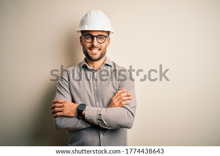 Young architect man wearing builder safety helmet over isolated background happy face smiling with crossed arms looking at the camera. Positive person.