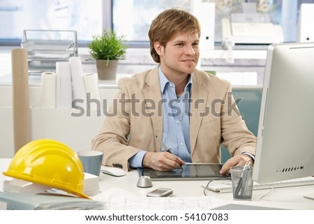 Young architect sitting at office desk, drawing pad, looking at screen.