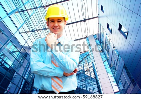 Young architect wearing a protective helmet standing on the building background