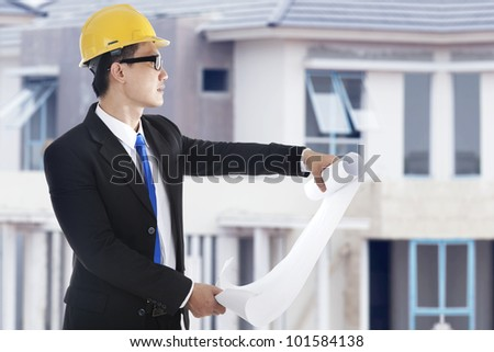 Young architect with blueprint inspecting the workplace